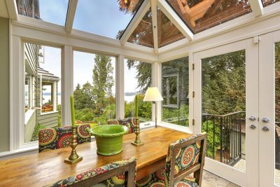 Sunroom patio area with transparent vaulted ceiling, wooden dining table with colorful chairs. Exit to backyard
